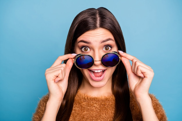 Close up photo of funky crazy girl touch her specs look see wonderful bargain scream unexpected unbelievable wear spring style clothing isolated over blue color wall