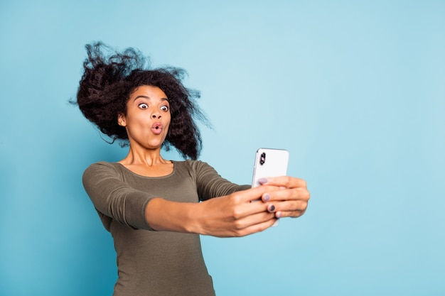 Close up photo of funny funky afro american girl feel impressed expression imagine she on roller coaster take selfie for blog blogger influencer wear style outfit isolated blue color wall