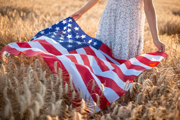 Close-up photo of girl holding flag of usa on ripe rye or wheat. independence day of usa