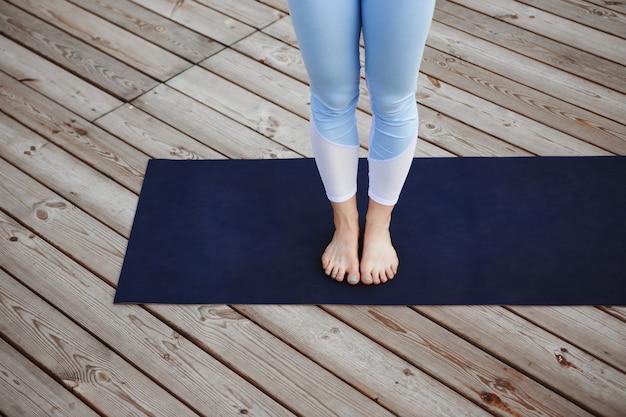 Chiuda sulla foto delle gambe della ragazza sopra il pavimento di legno