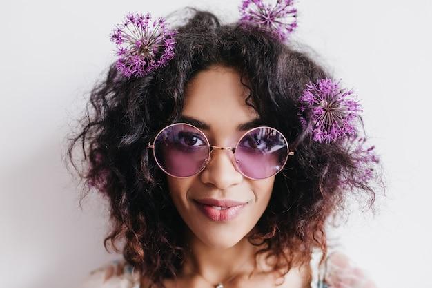 Foto del primo piano della donna africana felice che posa con i fiori nei capelli. ritratto dell'interno della ragazza nera soddisfatta in occhiali da sole isolati.
