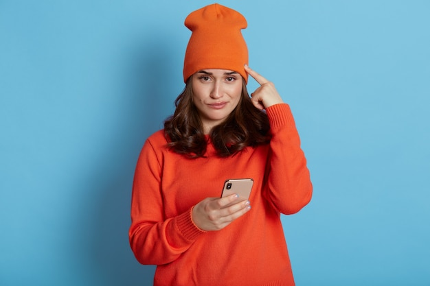 Close up photo of gorgeous girl with dark hair, reading something on her smart phone with puzzled face expression and holding her head with her index finger, wearing cap and sweater.