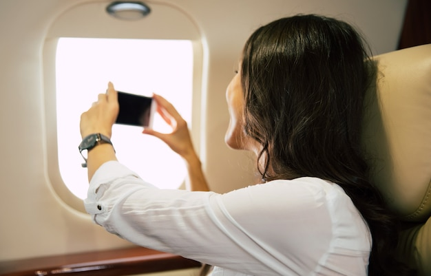 Close-up photo of a gorgeous woman in formal clothes, who is looking through the window and taking a photo with a smartphone, while sitting in her window seat, flying first class.