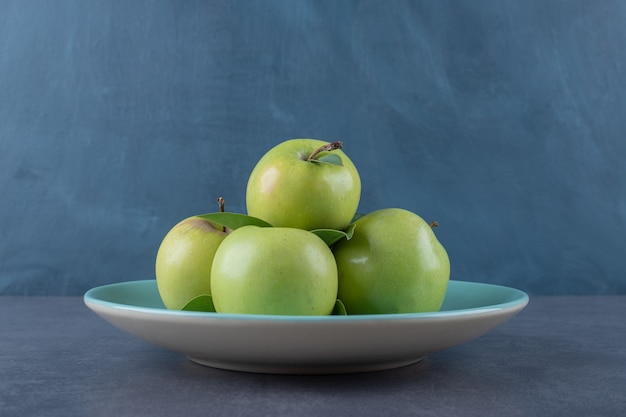 Close up photo of green apple on plate over grey background.