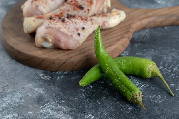 Primo piano foto di peperoncino verde e cosce di pollo crude. su sfondo grigio.