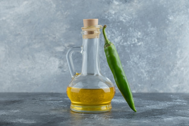 Close up photo of green hot pepper with bottle of oil on grey background