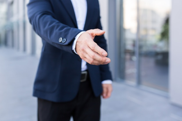 Close-up photo of greeting male businessman handshake in business suit