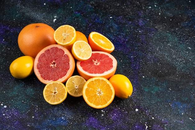Foto ravvicinata di fette di pompelmo e limone tagliate a metà sul tavolo scuro.