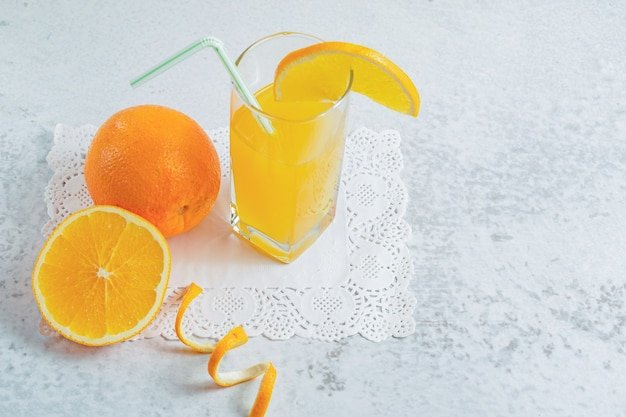 Close up photo of half cut or whole fresh orange with glass of juice on grey wall.