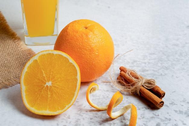 Foto ravvicinata di metà tagliata o intera arancia fresca.