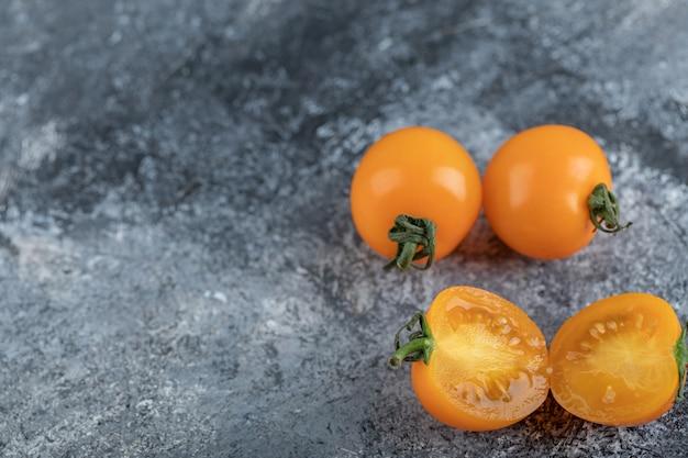 Primo piano foto di pomodori gialli interi o tagliati a metà. foto di alta qualità