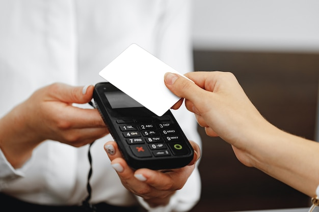 Close up photo of hand of customer paying with contactless credit card