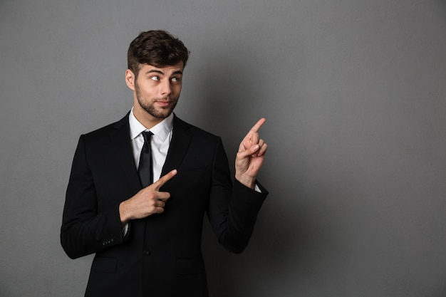 Close-up photo of handsome brunette man in black suit pointing with two fingers upward