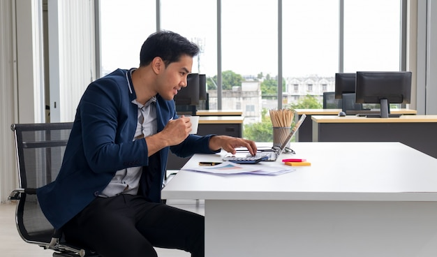 Close up photo handsome he him his guy hold hands arms hot beverage coffee toothy beaming smile speak talk tell say skype online meeting look notebook table sit office chair