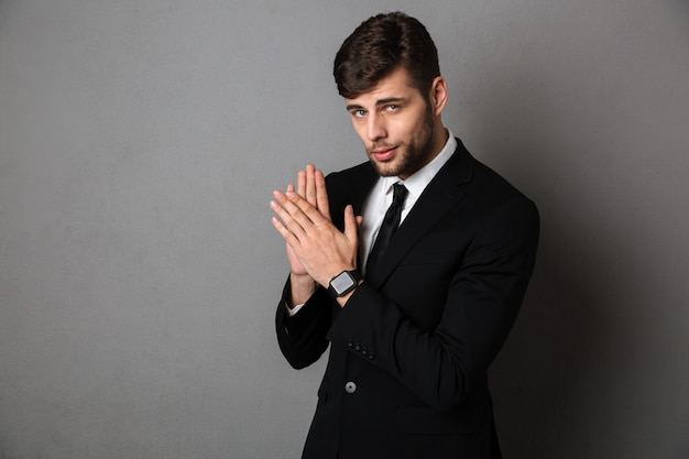 Close-up photo of handsome young man in black suit clap in hands