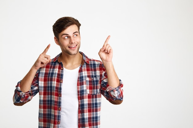 Close-up photo of happy attractive young man in checkered shirt pointing with two fingers, looking aside