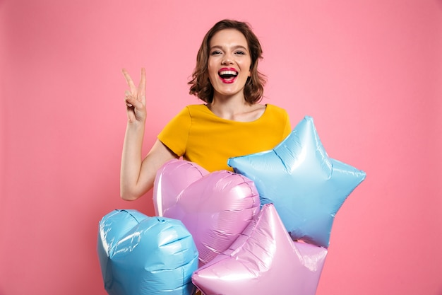 Close-up photo of happy birthday girl with red lips holding balloons, showing peace gesture,