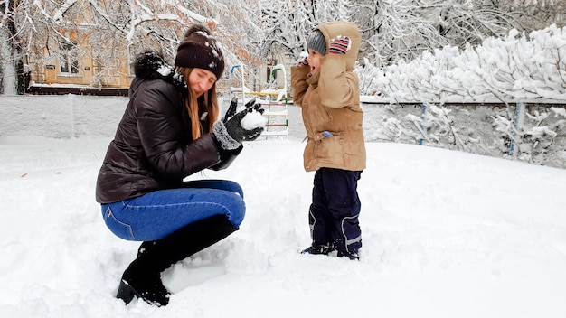 Close up photo of happy smiling young mother in broun coat and hat with her pretty son in beige jacket have fun to playing the snow balls with snow on the playground in the park