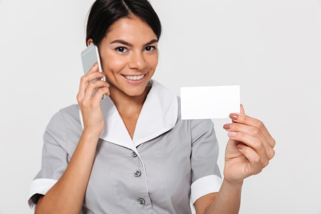 Close-up photo of happy young maid in gray uniform speaking on phone while showing empty sign card