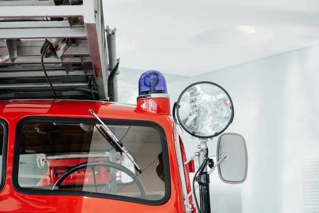 Close up photo of headlights. front of the red polished fire truck standing indoor at exhibition.