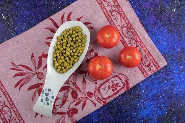 写真をクローズアップ。テーブルの上の健康的な成分。缶詰のエンドウ豆とトマト。