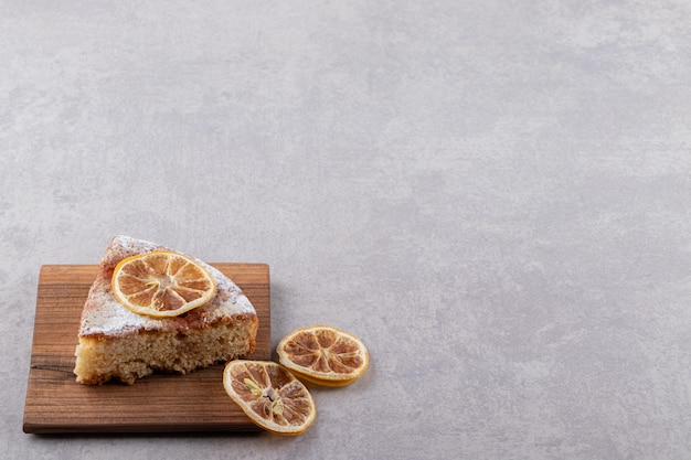Close up photo of homemade cake slice with dried lemon slices on wooden board.