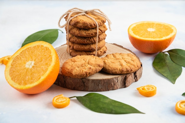Foto ravvicinata di biscotti fatti in casa su tavola di legno e arancia tagliata a metà con foglie su tavolo bianco.