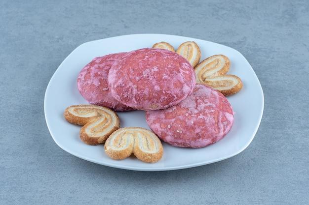 Foto ravvicinata di biscotti rosa fatti in casa sul piatto in ceramica bianca.