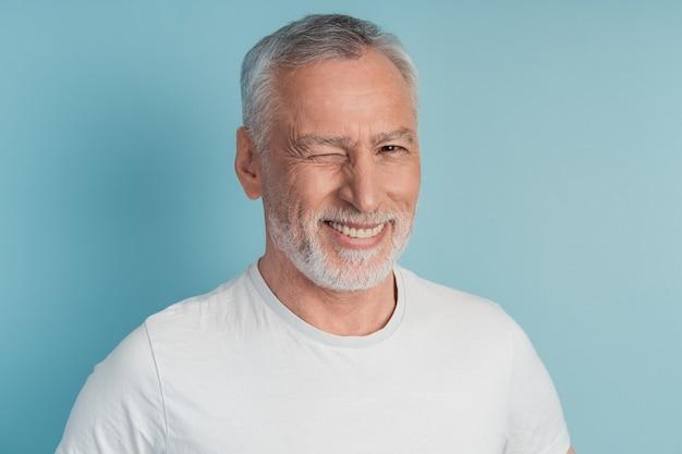 Close up photo of imposing old man winking