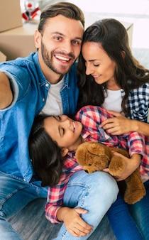 写真を閉じる、楽しい家族が段ボール箱の山の前にある新しい家で一緒に自分撮りをしています