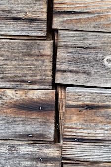 A close-up photo of a junction of boards that are the wall of an old wooden barn in the countryside
