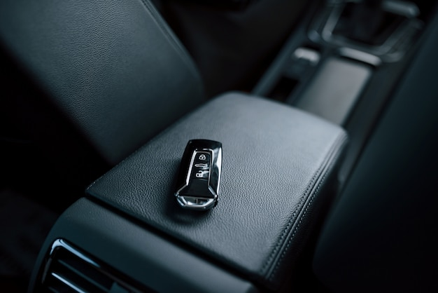 Close up photo of keys lying donw inside brand new modern car