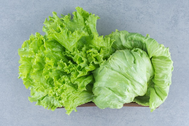 Close up photo leaves of lettuce on the grey background in basket.