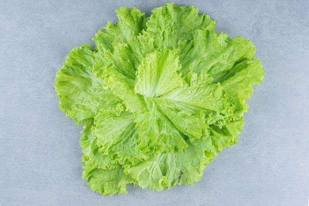 Primo piano foto foglie di lattuga su sfondo grigio.