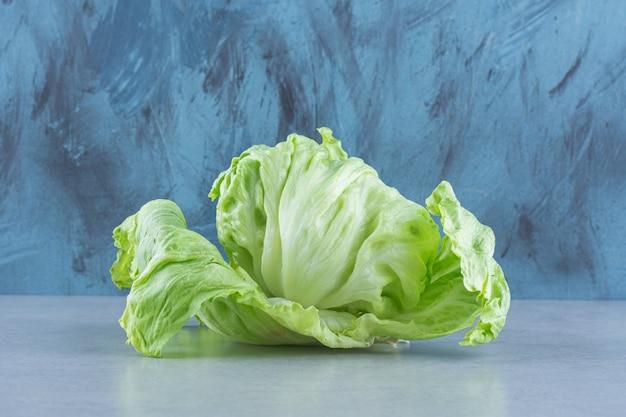 Крупным планом фото листья салата на сером фоне.