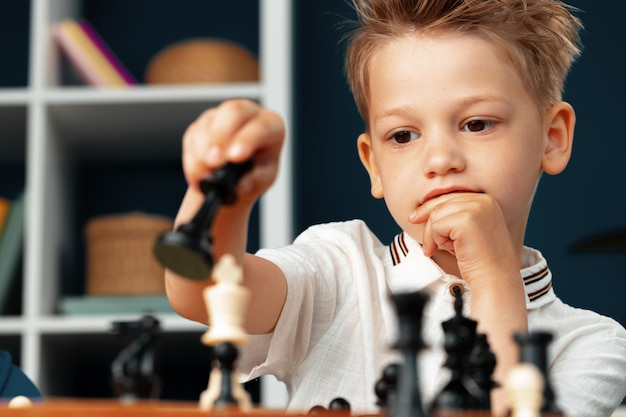 Close up photo of a little boy playing chess
