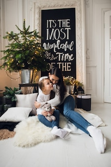 Close-up photo of little girl in knitted sweater kiss her mother while sitting on sofa at christmas