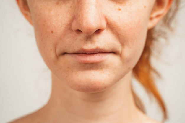 Close up photo of lower face of redhead young woman. isolated over white background. natural beauty and health.