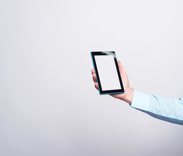Close up photo of male hand holding tablet with empty white screen.