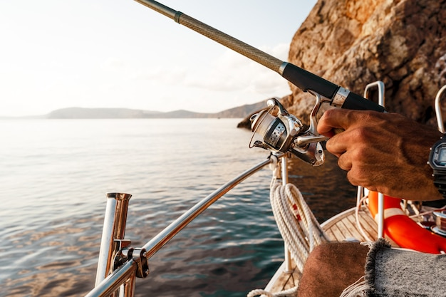 Close up photo of male hands holding fishing rod while fishing on sailboat in open sea