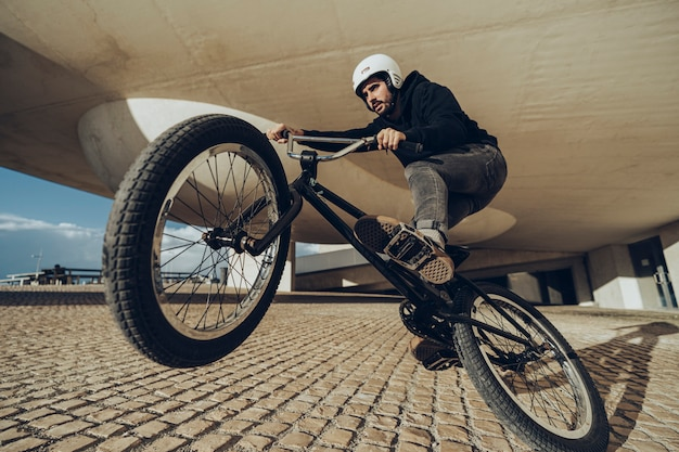 Close up photo of a man doing a wheelie in front of the camera.