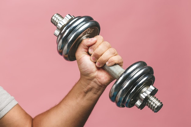 Close up photo of man grabs a heavy dumbbell