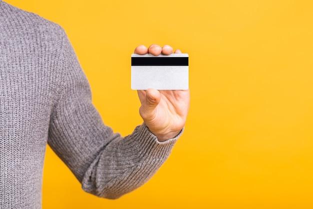 クローズアップ写真、黄色の背景で隔離のクレジットカードを持っている男の手。