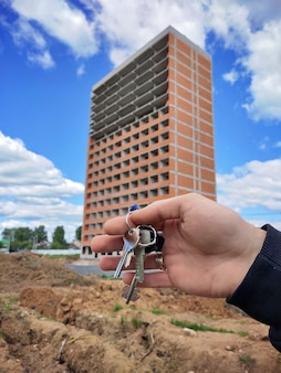 Close-up photo of a man`s hand holding the keys to a new house on the background of a modern residential building