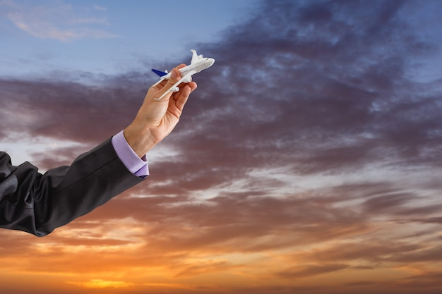 Close up photo of man's hand holding toy airplane against blue sky with clouds