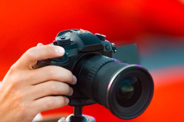 Close up photo of man shooting video with camera outdoor