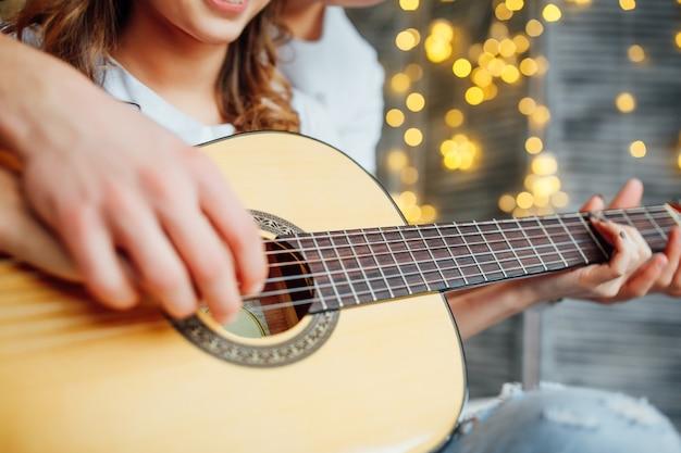 写真をクローズアップ。アコースティックギターの弾き方を女の子に教える男