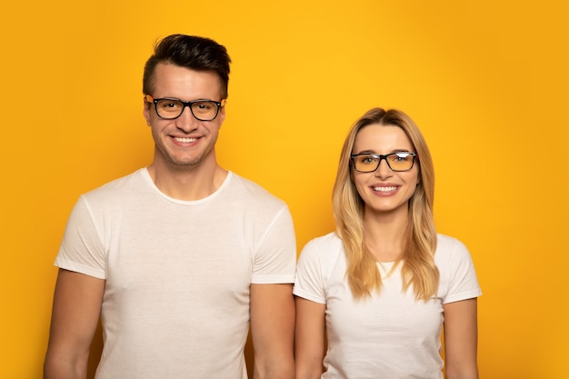 Close-up photo of a man and woman, posing in front of white t-shirts and glasses and smiling while looking in the camera