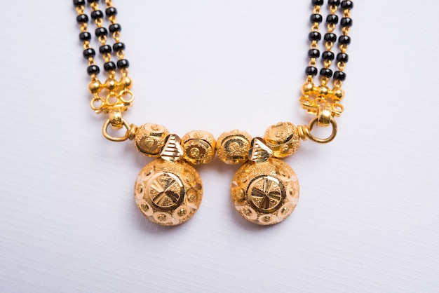 Close-up photo of a mangalsutra or necklace which is to be worn by a married hindu women over white background