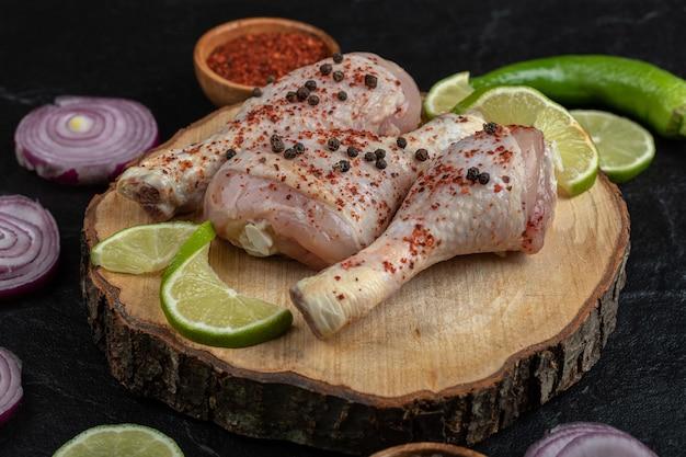 Primo piano foto di cosce di pollo marinate con verdure su tavola di legno.